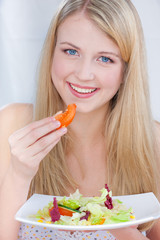 Pretty blue eyes woman eating tomato and holding salad on plate