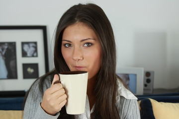 Young woman with beautiful face is having her tea/coffee