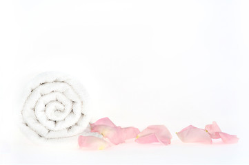 A shot of roll of towel with petals in a spa isolated on white