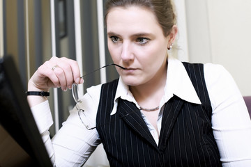 Concentrated businesswoman holds glasses with mouth hand