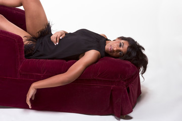 Glamorous model Afro American woman on red couch