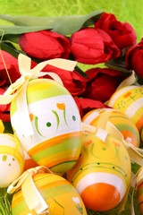 Easter egga with red tulips on green spring background