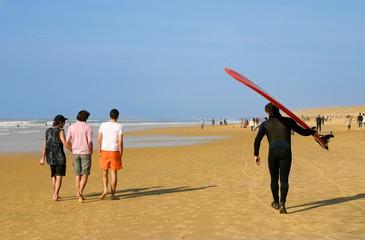 marcheurs et surfeur sur la plage