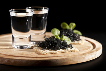 served place setting: vodka and sandwiches with black caviar on