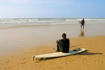 surfeur assis sur sa planche