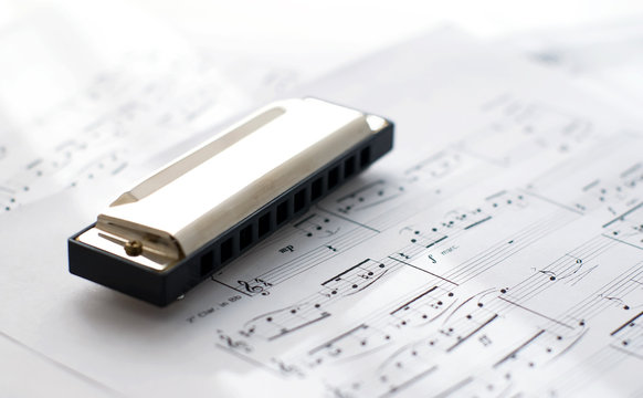 harmonica on sheets with blues notes lit by sunlight