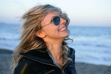 Blond girl with sunglasses on the beach