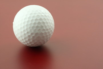 golf ball on red surface