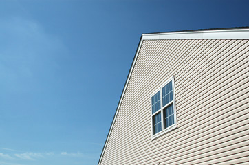 Side of new house showing peaked roof and blue sky.