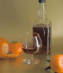 Glass of brandy, bottle and fruit on gold background