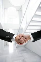 Businessman handshake on modern white office