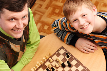 father with son play in chess