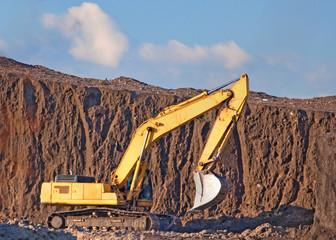 Large yellow excavator digging through a mound of dirt