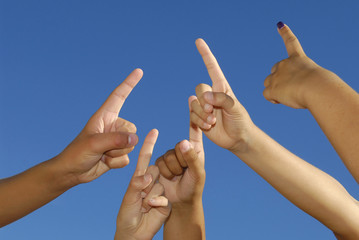 Several hands pointing high, with a blue sky
