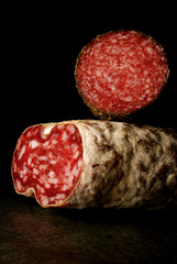 Salami and saucisson on a black bg