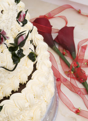 Detail of birthday cake with flowers and ribbon