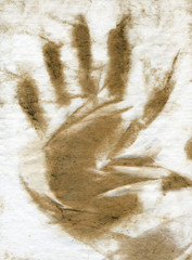 Dirty brown hand print against rough paper texture