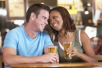Couple Drinking Beer Together In A Pub