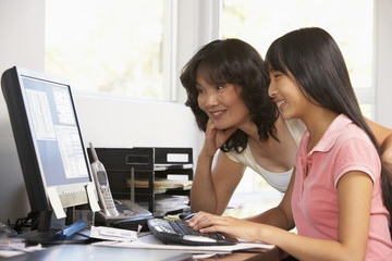 Woman Watching Her Daughter Use A Computer