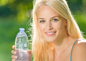 Portrait of smiling woman with bottle of water, outdoors