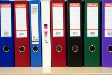 Multicolored folders standing on a shelf