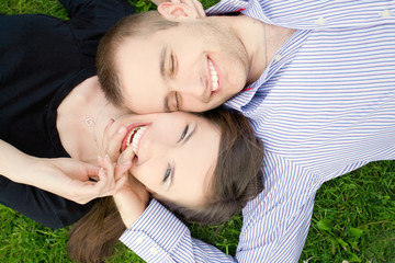 Smiling young couple is cuddle on a green meadow