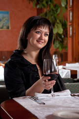 Charming brunette girl in a restaurant with a glass of red wine