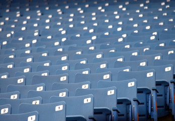 Row of blue empty seats at a sports arena
