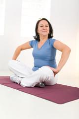 Woman sitting cross-legged on mat
