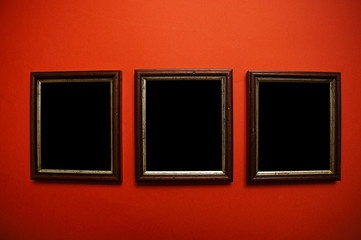 empty picture frames on red wall