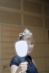 frau in büro betrachtet sich in spiegel mit krone