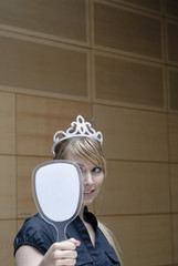 junge frau in büro betrachtet sich in spiegel mit krone