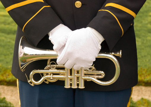 Uniformed military bugler's gloved hands over trumpet.