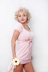 pretty woman in pink dress holding flower.