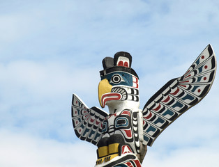 Detail of a North American Totem Pole against a blue sky