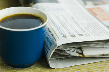 Close up photo cup of coffee and newspapers