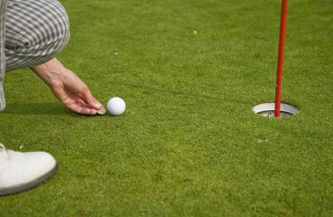joueuse de golf marque la balle sur le green