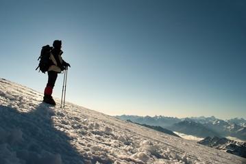 Figure of climber on a background sunbeams and mountain backbone