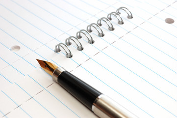 A gold pen on a spiral-bound notepad