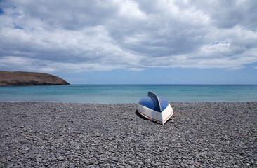 fuerteventura, old overturned boat on black volcanic stone beach