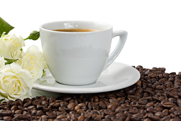 A cup of coffee with white roses and coffee beans isolated on wh