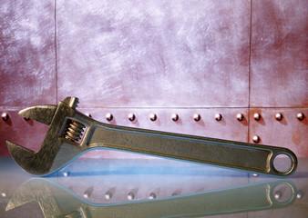 Adjustable spanner on a background of a metal design.