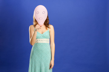 girl hiding over pink surprised balloon