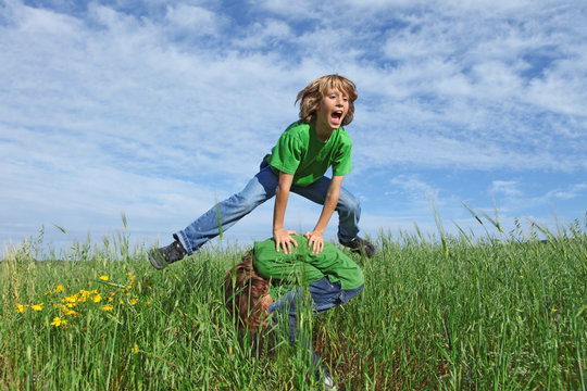 healthy kids playing leapfrog outdoors in summer