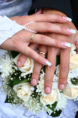 Hands with rings on a bunch of flowers