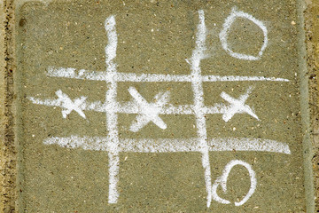 Tic tac toe game drawn with chalk on asphalt