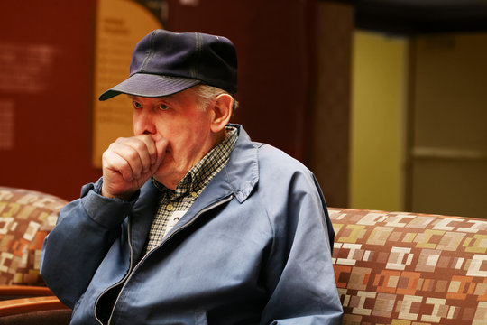 Elderly man couching in doctor's waiting room