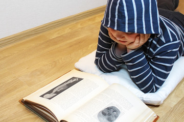 Boy is reading an old book