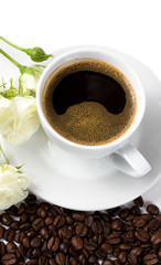 A cup of coffee with white roses and beans