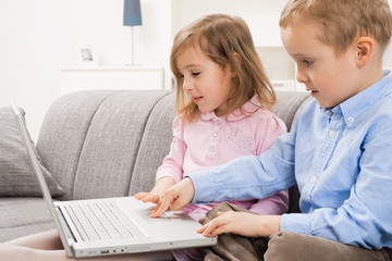 Little boy and girl using laptop